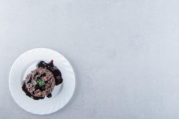 하얀 접시에 시럽으로 장식된 초콜릿 케이크 한 조각. 고품질 사진