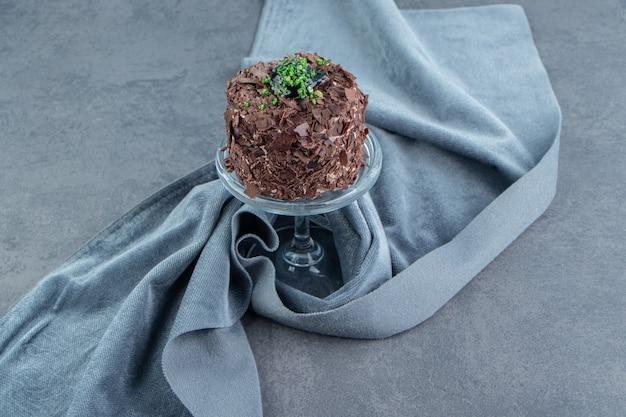 유리 접시에 초콜릿 케이크의 조각입니다.
