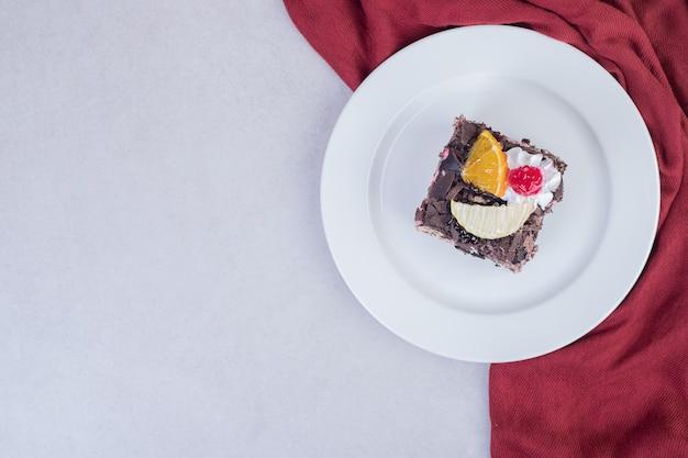 Кусочек шоколадного торта на белой тарелке с красной скатертью.