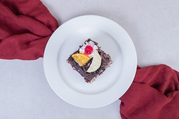 Кусок шоколадного торта на белой тарелке с красной скатертью.