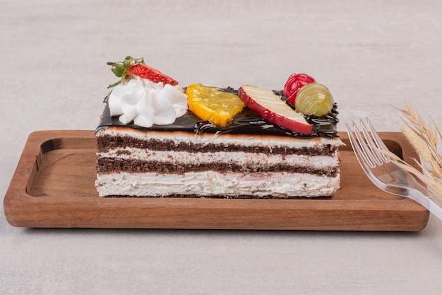 과일 조각으로 나무 보드에 초콜릿 케이크의 조각.
