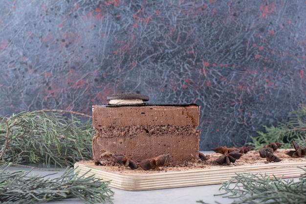 Кусочек шоколадного торта с гвоздикой на деревянной доске. фото высокого качества