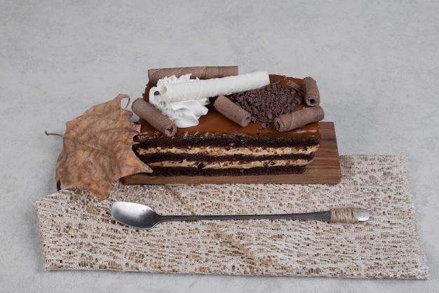Кусок шоколадного торта с листом и ложкой на мраморном столе. фото высокого качества