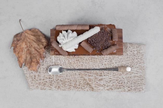 大理石のテーブルの上に葉とスプーンでチョコレートケーキのスライス。高品質の写真
