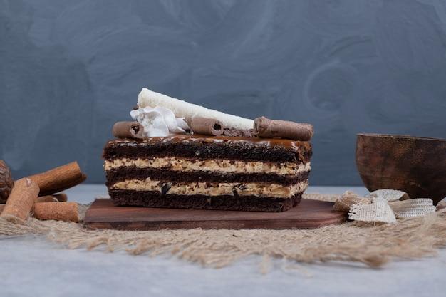 Кусок шоколадного торта с листом на мраморном столе. фото высокого качества