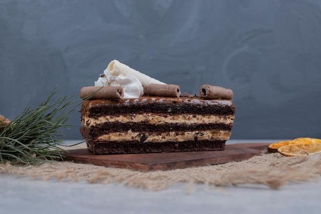 大理石のテーブルの上に葉とチョコレートケーキのスライス。高品質の写真