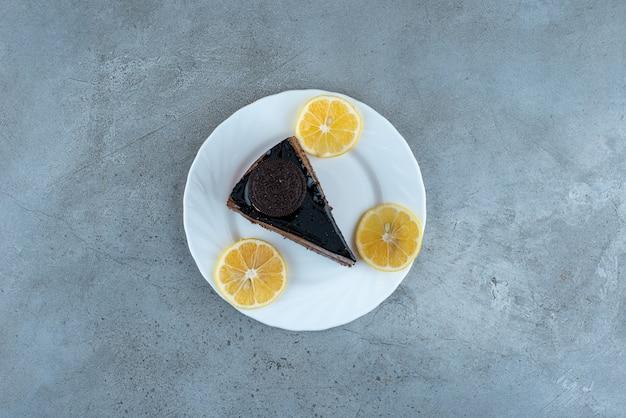 Кусочек шоколадного торта с ломтиками лимона на белой тарелке. фото высокого качества