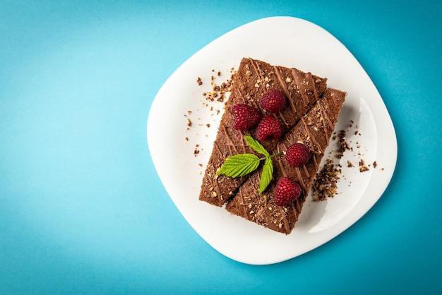 Кусочек шоколадного торта с молочной начинкой и малиной на белой тарелке на синей поверхности.