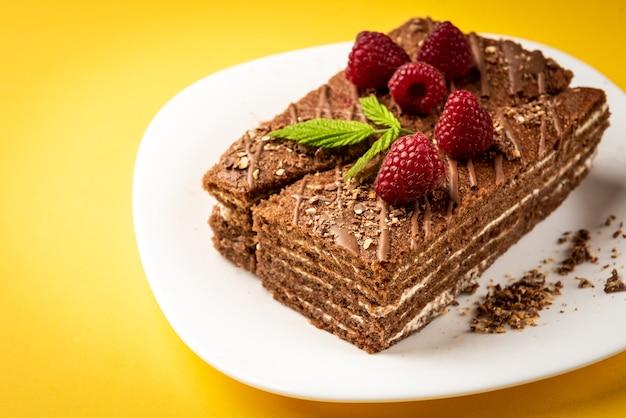 Кусочек шоколадного торта с молочной начинкой и малиной на белой тарелке на желтой поверхности.