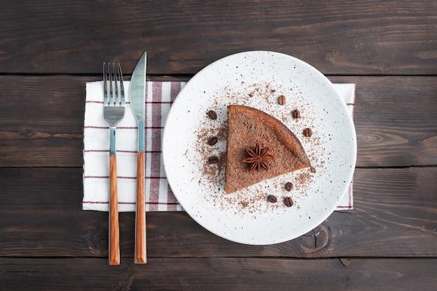 プレート上のチョコレートカードキャセロールのスライス、チョコレートとコーヒーのケーキの一部。ダークウッドの素朴なテーブル。トップビューコピースペース