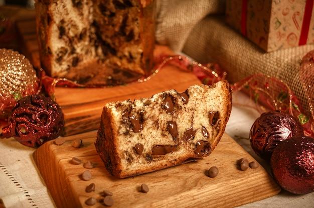 クリスマス飾りと木製のまな板にチョコレートパネットーネのスライス