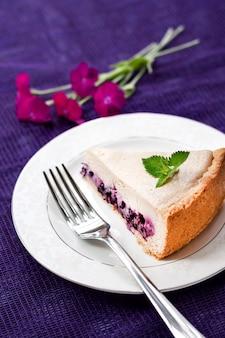 Кусочек кофейного торта с черникой на белой тарелке.