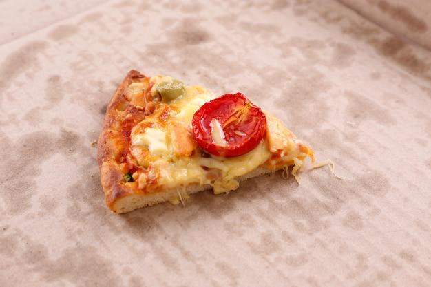 段ボールのおいしいピザのスライス、クローズアップ