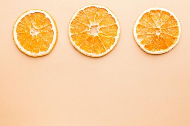 텍스트에 대 한 공간을 가진 밝은 갈색 배경에 말린 된 오렌지의 조각. 미니멀리즘, 음식 개념.