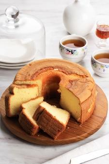Кусочек пушистого ванильного шифонового торта или бисквитного торта на деревянной тарелке, подается с чаем и медом. яркая концепция фотографии еды для пекарни. выбранный фокус