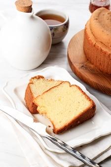 ふわふわバニラシフォンケーキまたはスポンジケーキを木の板にスライスし、お茶と蜂蜜を添えて。パン屋のための明るい食べ物の写真のコンセプト。選択されたフォーカス