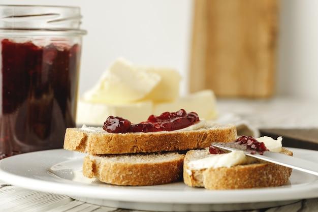 Кусочек свежего хлеба с маслом и джемом на столе