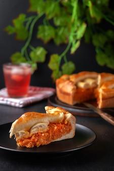 Кусочек свежего домашнего пирога с капустой с освежающим охлажденным летним фруктовым напитком и растениями позади