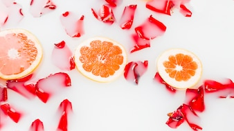 Slice of grapefruits and flower petals floating on milk