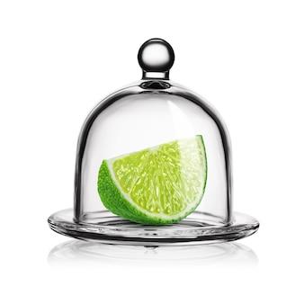 흰색 배경에 분리된 유리 벨 항아리에 녹색 라임 조각.