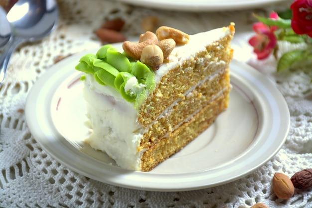 Кусочек домашнего морковного торта с глазурью из сливочного сыра на белой тарелке