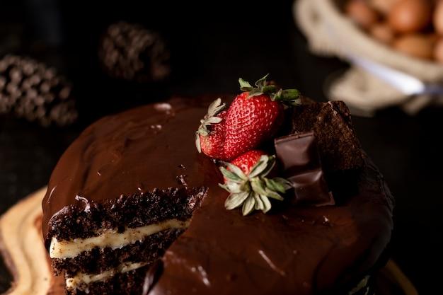 Кусочек домашнего шоколадного торта с вкусной клубникой на столе