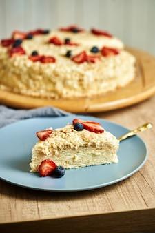 Кусок домашнего торта наполеон на тарелке. деревянный фон
