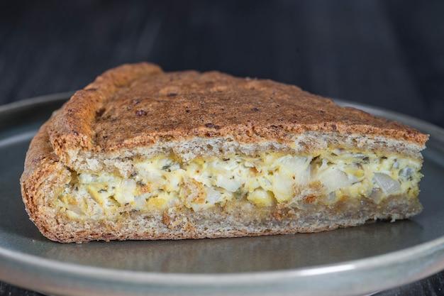 Ломтик домашнего лукового пирога с запеченным кремом и яичным пирогом, покрытый сыром и зеленью, крупный план