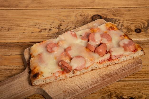 木製のまな板にフランクフルトと自家製ピザのスライス。
