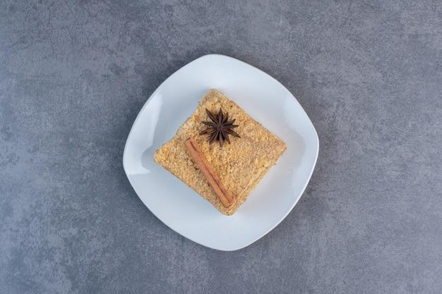 Кусочек медового торта на белой тарелке.