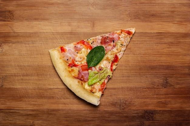 Кусок горячей свежей пиццы на деревянном