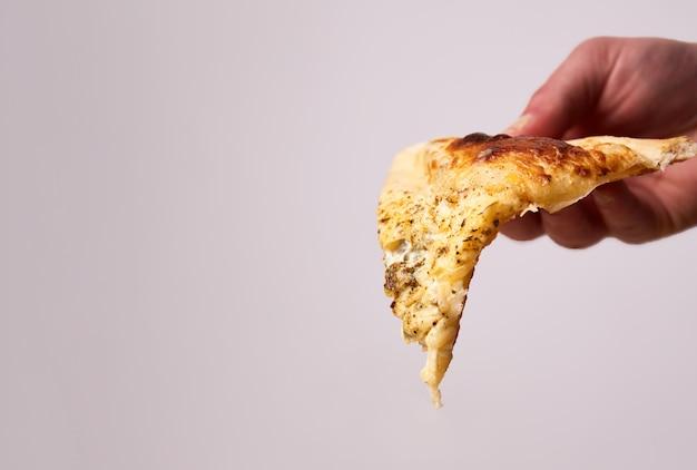 ホットピザのスライスチェダー、パルメザンチーズ、モッツァレラチーズ、トマトソースを手にした4つのチーズ。ベジタリアンピザ