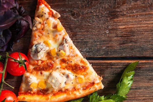 木のテーブルで熱いピザのスライス。