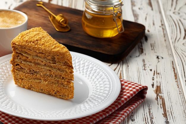 Кусочек слоеного медового торта на тарелке