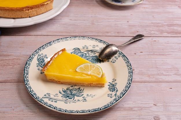 나무 테이블에 오래 된 접시에 레몬 파이의 조각