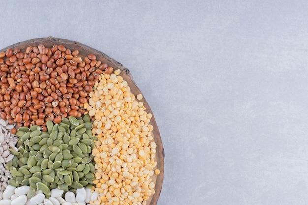 Кусочек бревна, покрытый красной фасолью, пепитасом, темно-синей фасолью, красной чечевицей и очищенными семечками подсолнечника на мраморной поверхности