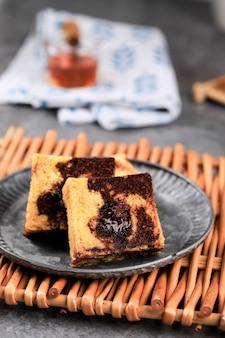대리석 여행 케이크 조각, 중앙에 녹인 초콜릿이 있는 사각 케이크. 소박한 접시에 제공