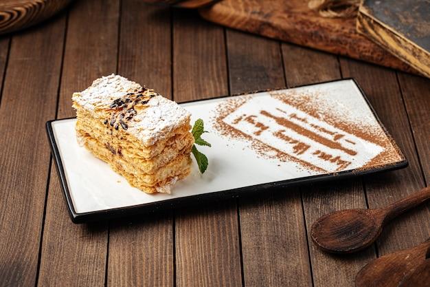 Кусочек торта наполеон на украшенной тарелке
