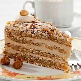 커피 한 잔과 함께 noisette 케이크의 조각을 닫습니다