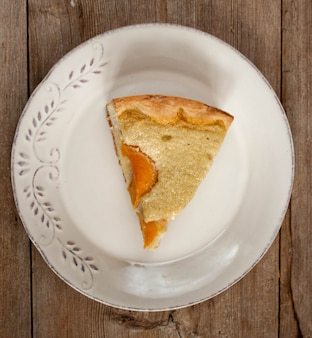 나무 테이블 상단보기 평면 누워에 흰색 접시에 오픈 복숭아 살구 파이의 조각