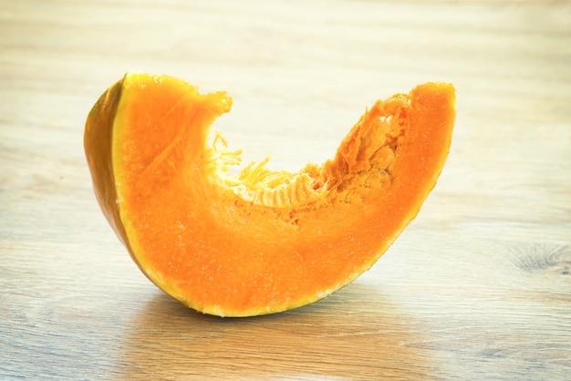 Кусочек апельсиновой тыквы на деревянном столе