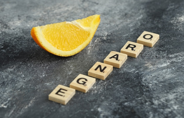 オレンジと綴られた木製の文字が付いたオレンジのスライス。