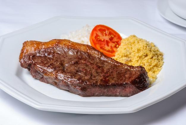 쌀, 밀가루, 토마토와 함께 접시에 피카냐 고기 바베큐 조각. 브라질 요리법.