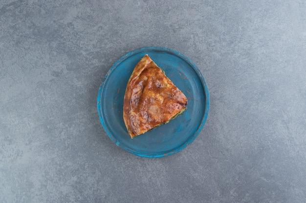 黒のまな板に緑を詰めたパイのスライス。 無料写真