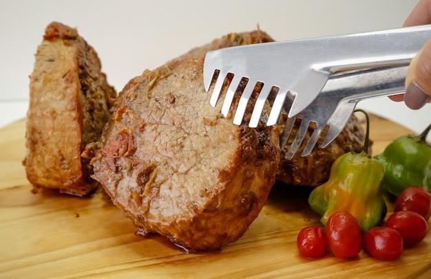 ナイフとカトラリーで木の板に鍋で調理した肉のスライス