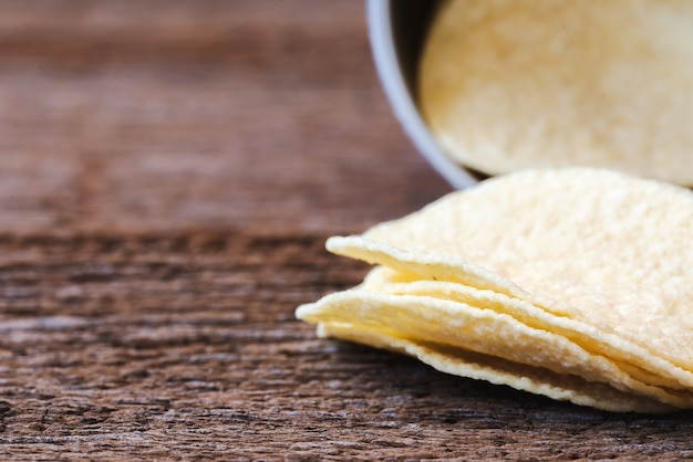 Кусочки чипсов из картофельных чипсов в бумажной тубусной коробке на деревянных досках. макросъемка