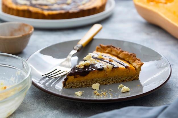Кусочек тыквенного пирога. вид сверху сквош-тарт. домашняя осенняя еда. фон пекарни