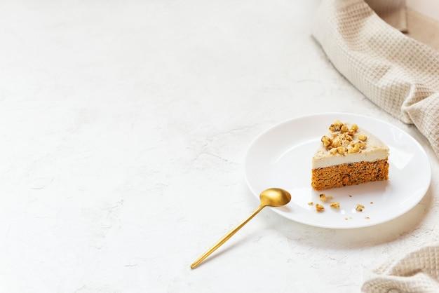 白いプレートにココナッツクリームとクルミを添えた生のキャロットケーキのスライス