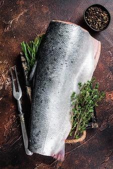 Ломтик сырой лососевой рыбы на деревянном подносе с тимьяном