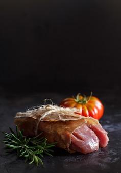 Кусочек сырого стейка из индейки с розмарином и помидорами на темном столе крупным планом